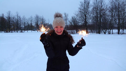 Young woman with burning sparklers at snowy park, winter evening Footage