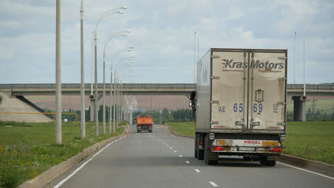 Dirty Lorry Drives along Modern Highway with Small Traffic Footage