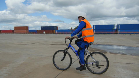Worker in Orange Vest Rides on Bike along Plant Yard Footage