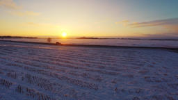 Winter road. Aerial footage. White fields covered with snow. Sunset