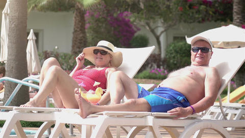 Video of senior couple relaxing on the sunbeds in real slow motion Footage