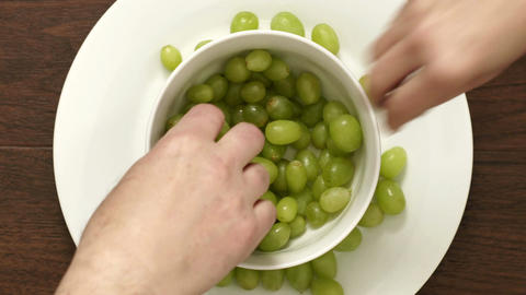 Overhead of Couple Eating Green Grapes From Bowl Closeup Footage