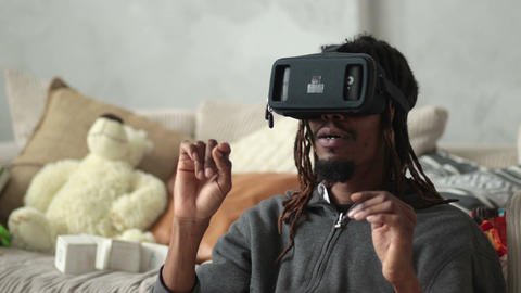 Excited man using virtual reality goggles at home ビデオ