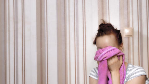 4K Girl Wipes Her Face With Towel and Smiles in Living Room Against The Footage