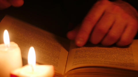 man read book in darkness with candles. Leaf through by isolated hands. Dark ver Live Action