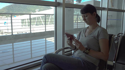 Woman checks her ticket in the airport waiting area Footage