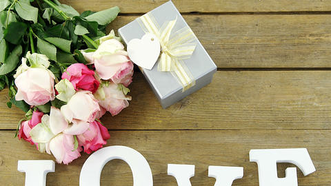 Gift box with bunch of roses and love alphabet on wooden plank Footage