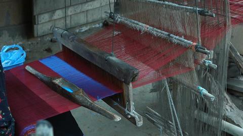 Old woman working on wooden weaving loom machine Footage