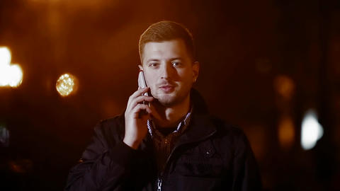 cute guy in the night with the phone. guy working the phone in the air hd Filmmaterial