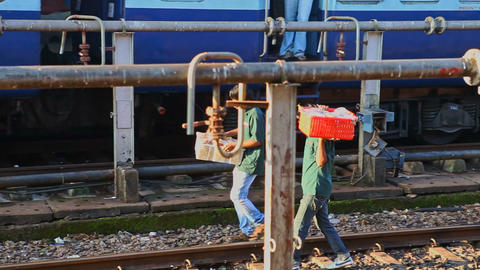 Men with Boxes Walk along Railway Tracks by Metal Constructions Footage