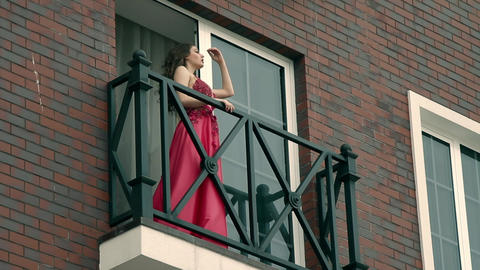 beautiful girl on the balcony looks into the distance Footage