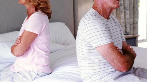 Upset senior couple sitting back to back on bed Live Action