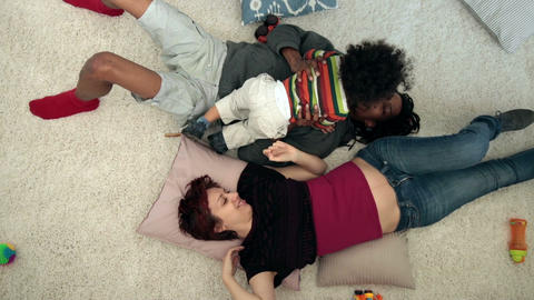 Happy mixed family with child lying on the floor Footage