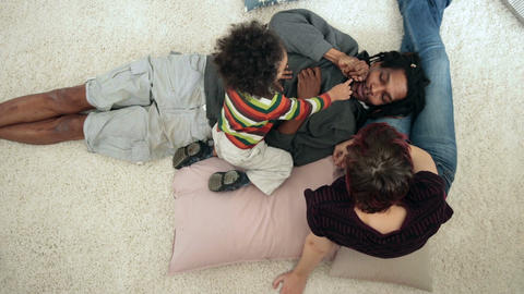 Diverse family with toddler boy lounging at home Footage