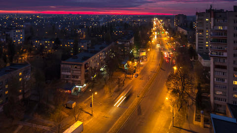 Bright crimson red sunset in the city, traffic of cars, light up lights, lights  Footage