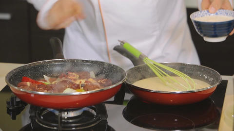 Chef putting meat in pan with vegetables Footage