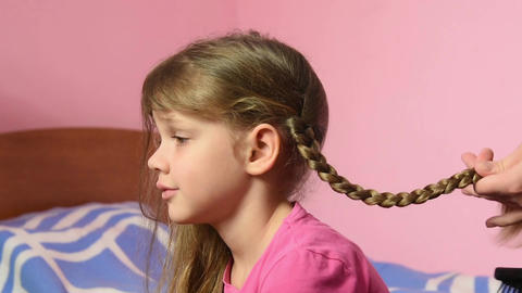 Mom braided pigtail daughter and kissed her on the cheek Footage
