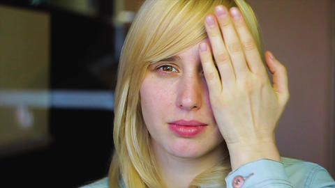 Blonde with different eyes looks at the camera and Remove her hand, heterochromi Footage