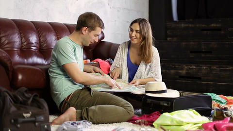 Young couple planning vacation trip with map Live Action