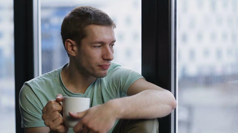 Relaxed young hipster drinking coffee near window ビデオ
