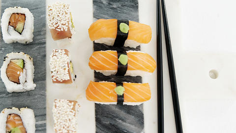 Set of assorted sushi served on gray stone slate Footage