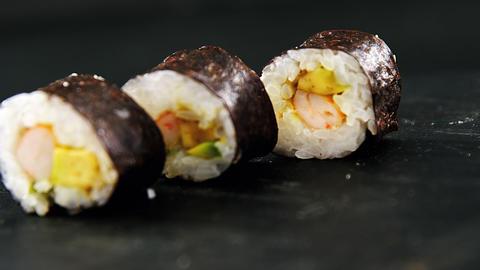 Maki sushi on black background Live Action