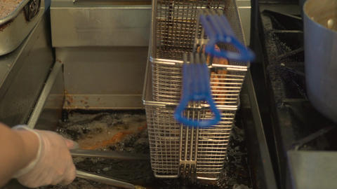 Chicken cutlets being removed from fryer Footage