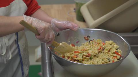 Large bowl of pasta salad being stirred Footage