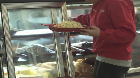 Employee puts food in deli case Footage