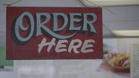 Pick up order here sign near food menu Footage
