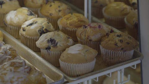 Freshly baked breafast muffins placed in case Footage