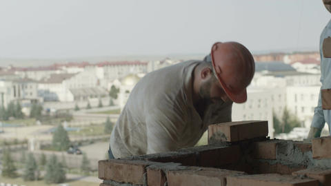 Stone Masons in Helmets Lay Bricks on Wall against City Footage