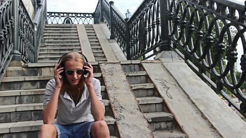 Listening to music while sitting on the stairs Live Action