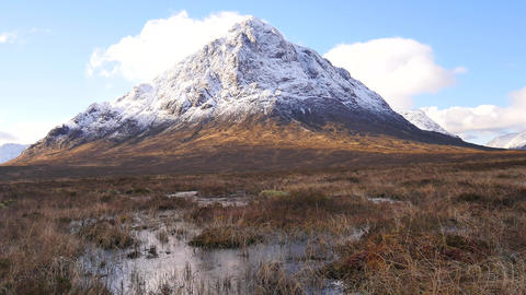 Sunny winter day on meadow at river Coupall at delta to river Etive. Snowy cone  Archivo