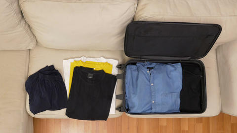 Top view timelapse of packing clothes into a suitcase Footage