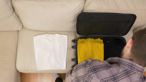 Man unpacking clothes from suitcase Footage