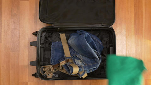 Man hurrying up to pack clothes into travel suitcase Footage