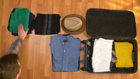 Top view timelapse of young man folding clothes in travel bag Footage