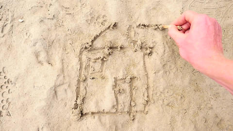 Hand draw with stick of wood home in the wet sand on the coast. Drawing of house Footage
