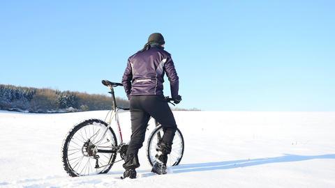 Winter biker pushing mountain bike on snow drift. Freeze sunny winter weather. B Archivo
