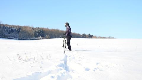Biker pushing mountain bike on snow drift. Freeze sunny winter weather. Biker is 영상물