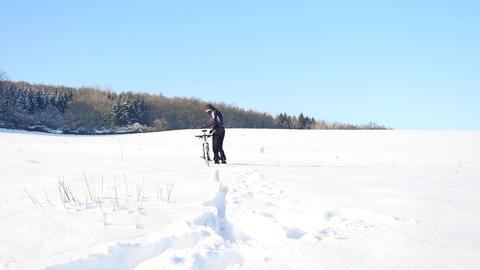 Biker pushing mountain bike on snow drift. Freeze sunny... Videos de Stock