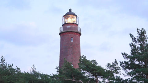 Shinning old lighthouse with dark clouds after sunset in background. Tower illum Footage