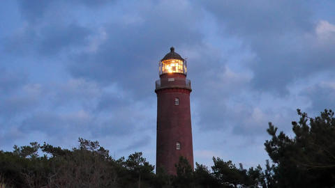Shinning old lighthouse above pine forest before sunset. Tower illuminated with  Footage