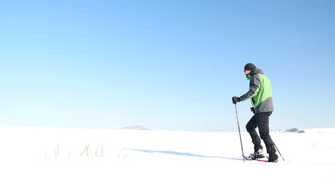 Winter tourist with snowshoes walk in snowy drift. Hiker in green sports jacket  Footage