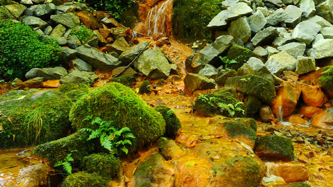 Stream water full of red ferric sediments. Cascades in stream, mossy boulders an 影片素材