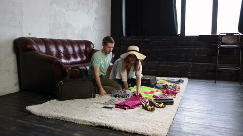 Young couple packing stuff into suitcase at home Live Action