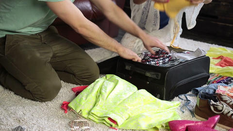 Couple packing clothes into suitcase for journey Live Action