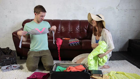 Couple packing for holiday trip and having fun Live Action
