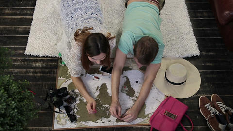 Young family marking places to visit on travel map GIF